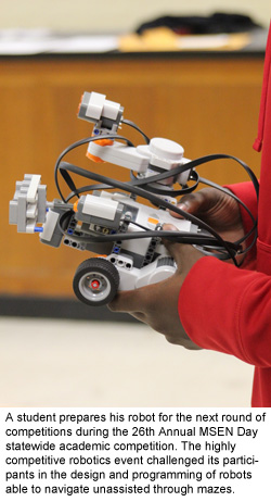 A student prepares his robot for the next round