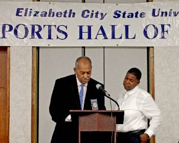 Deanna Price, right, receives her induction plaque from retired ECSU coach, Alvin Kelley.